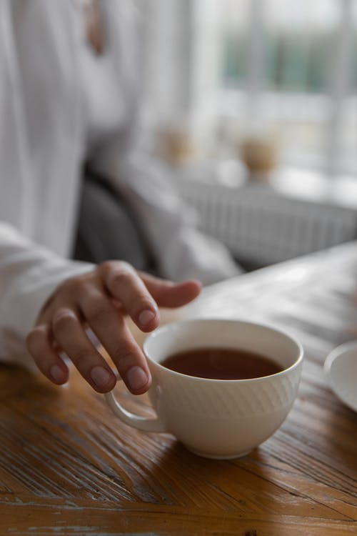 Crop faceless person holding cup of hot drink while sitting at wooden table at home