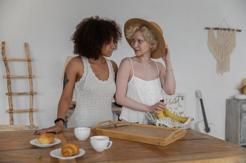 Multiethnic lesbian couple preparing products for breakfast