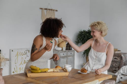 Cheerful multiracial lesbian couple in casual clothes sitting at table and preparing healthy breakfast while feeding each other