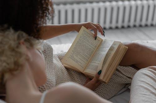 Woman Reading Book on White Textile
