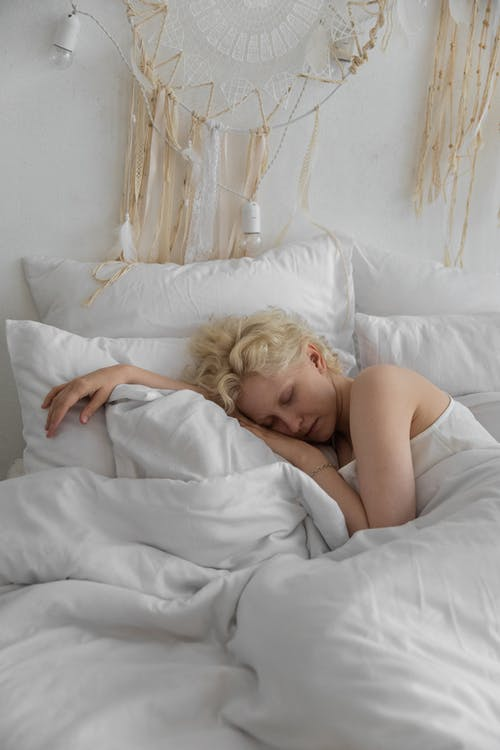 Sleepy woman resting on bed in morning