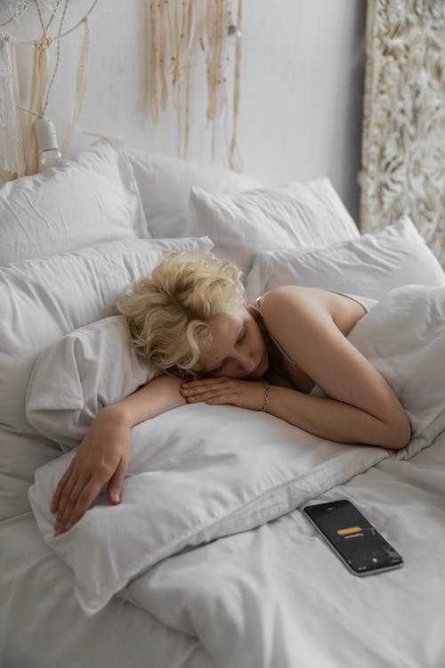Lazy female resting in bed under soft blanket with alarm on cellphone for waking up