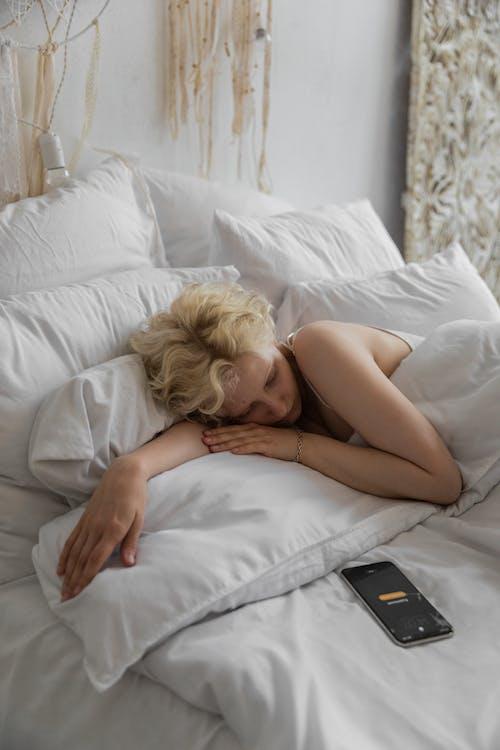 스마트 폰 알람과 함께 침대에 누워 잠자는 여자