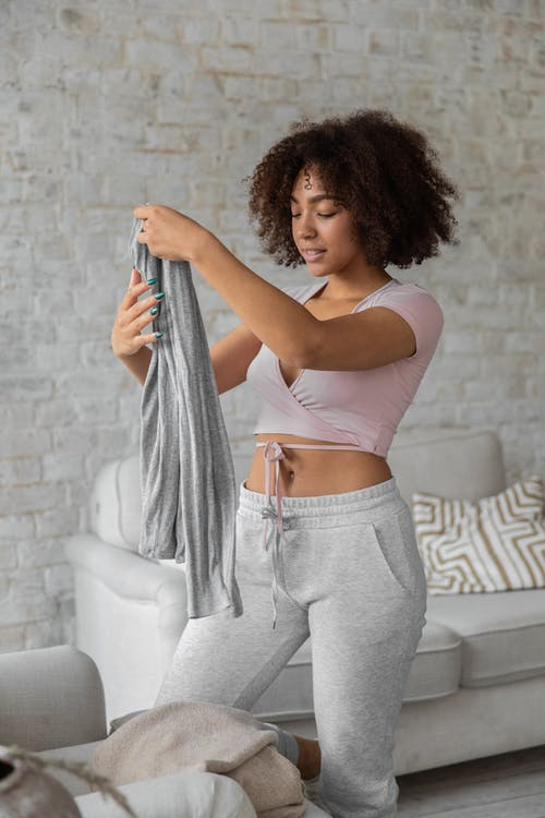 Smiling black woman folding clothes during housework