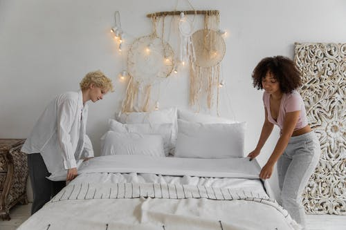 Diverse lesbian couple making bed together