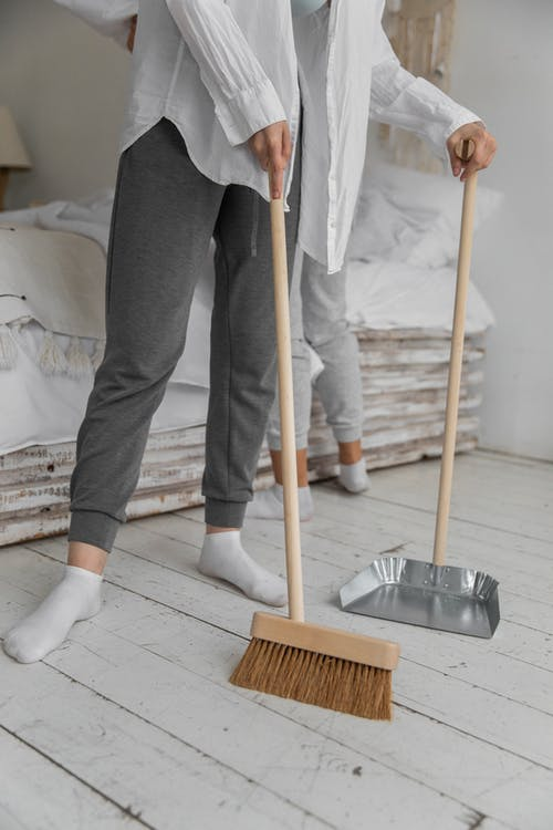 Anonymous women sweeping floor during housework at home