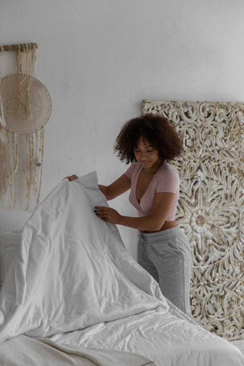 Side view of young fit African American female with curly hair in casual clothes making bed in cozy minimalist room in morning
