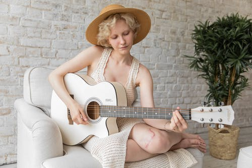 Calm woman playing acoustic guitar on armchair