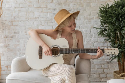 Calm woman playing acoustic guitar in cozy apartment