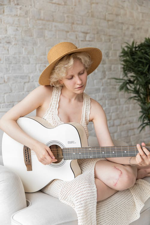 Focused female in hat and dress playing acoustic guitar while sitting on armchair near potted plant during rehearsal at home