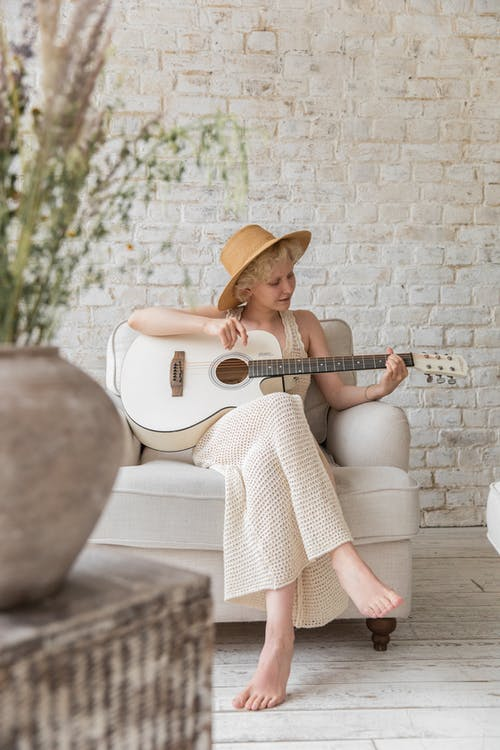 Full length of happy young stylish barefooted lady in dress and hat playing acoustic guitar while resting in armchair in cozy living room