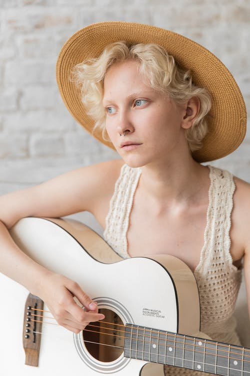 Stylish pensive young lady playing guitar against white brick wall