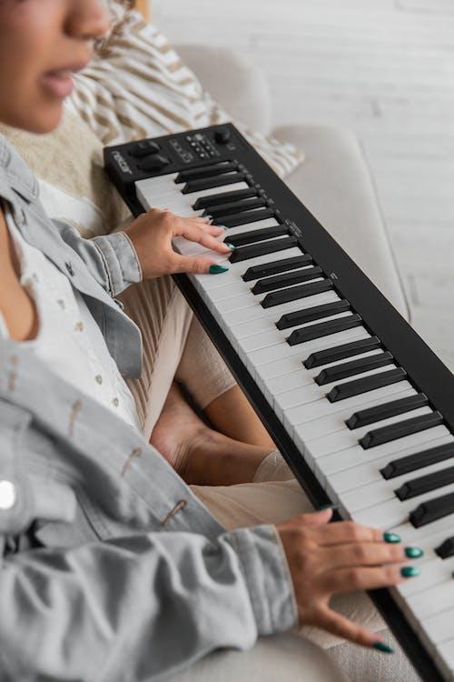 Crop ethnic lady playing synthesizer on sofa