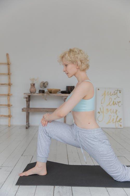 Slim Young Woman Performing Anjaneyasana Yoga Pose Sur Tapis à La Maison