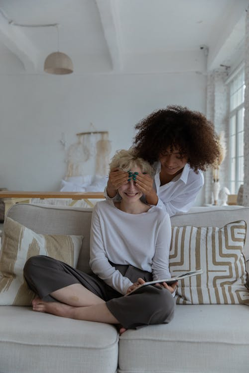 Cheerful young black lady covering eyes of girlfriend relaxing on sofa with book