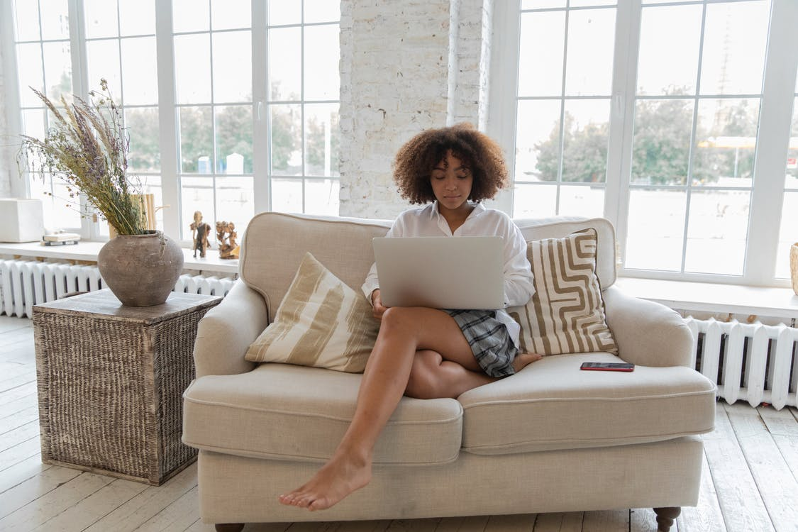 Full length of barefooted  young ethnic female freelancer with Afro hair in casual outfit sitting on comfortable sofa and working online on laptop in stylish apartment