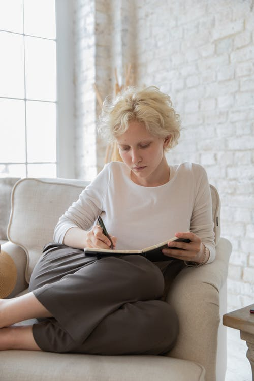 Concentrated young female author with short blond hair in casual outfit taking notes in diary while creating new story at home