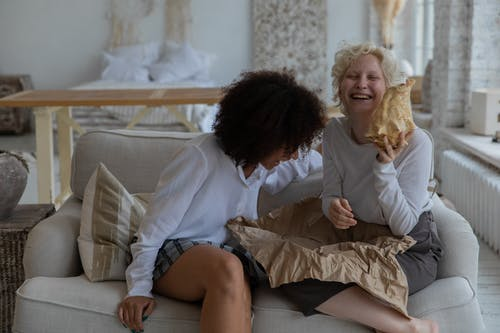 Cheerful young diverse women having fun while unpacking present on sofa