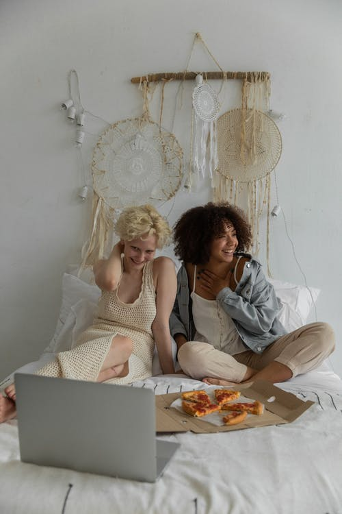Happy young multiethnic girlfriends in stylish clothes eating pizza and watching funny movie on laptop while resting on comfortable bed at home