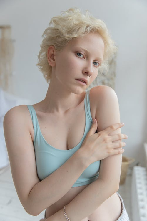 Alluring young lady looking at camera in bedroom