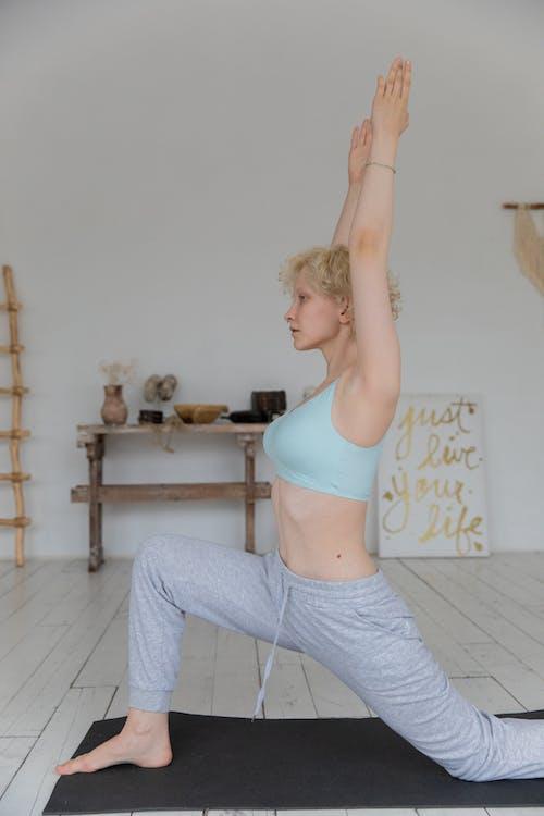 Jeune Femme Concentrée Effectuant Anjaneyasana Pose Pendant La Formation De Yoga à La Maison