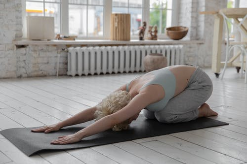 Anonymous woman stretching body in Extended Child s yoga pose