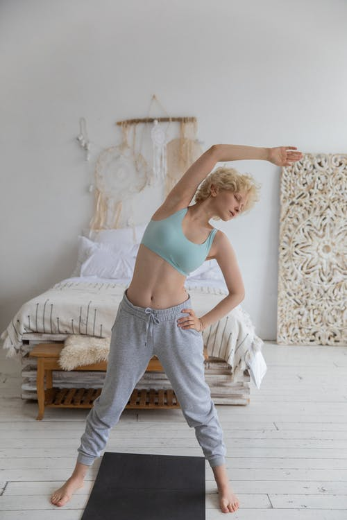 Full body of young slim female with short blond hair in sportswear doing Standing Side Bend Pose while warming up before practicing yoga in cozy bedroom