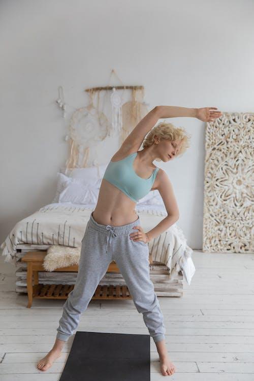 Fit Jeune Femme Qui S'étend Du Corps Avant La Formation De Yoga Dans La Chambre