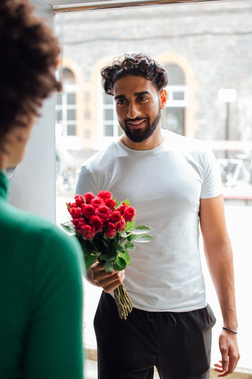 Man in White Crew Neck T-shirt Holding Bouquet of Red Roses