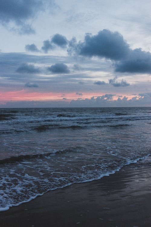Astonishing view of blue ocean with waves and sandy beach with colorful cloudy sky on horizon