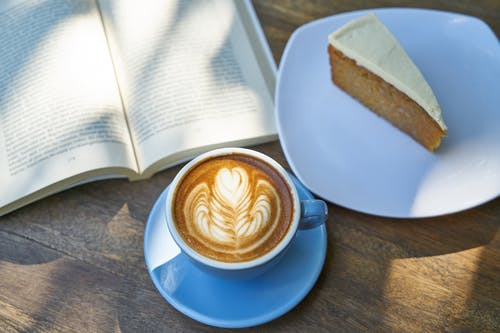 Coffee Latte Beside Book and Cake