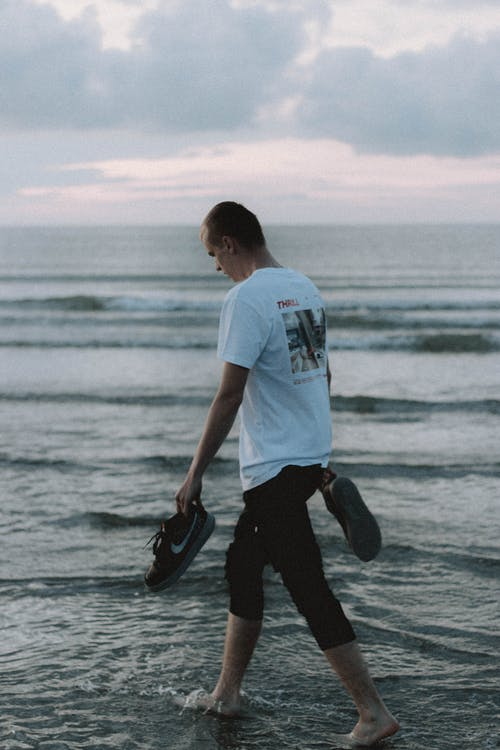 Back view of anonymous male tourist carrying sneakers while walking on wavy ocean under cloudy sky at sundown
