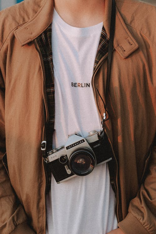 Crop man in casual wear with vintage photo camera