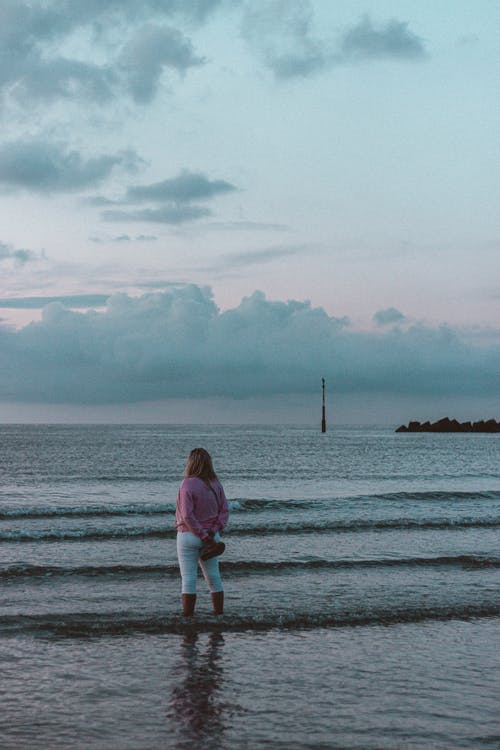 Anonymous tourist admiring seascape under sky in evening