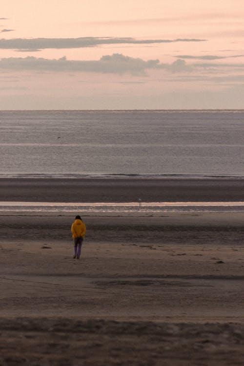 Back view of faceless traveler admiring ocean on sandy beach under cloudy sky at sundown