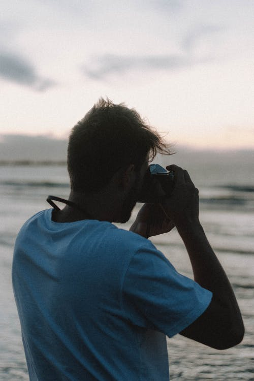 Anonymous man taking photo of sea in evening time
