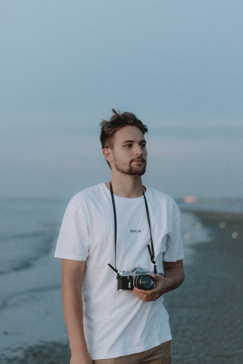 Thoughtful male in casual wear with photo camera in hand standing on shore near waving sea water and looking away