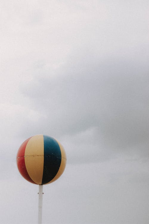 Big balloon with various colors located under cloudy gray sky in gloomy weather