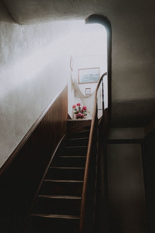 From bellow of narrow stairway with wooden steps and handrails leading to room with rays of sunlight