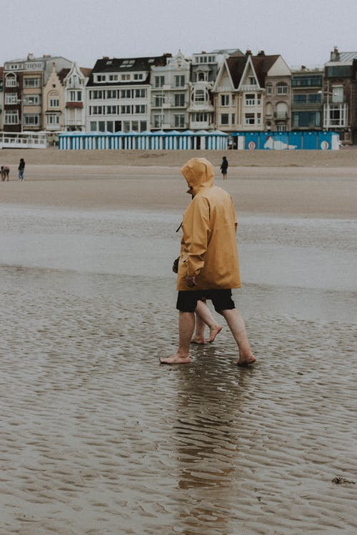 Side view of unrecognizable barefoot couple wearing raincoats strolling along seashore with feet in water on rainy day