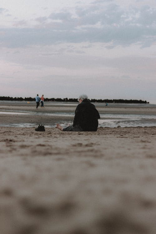 Anonymous person sitting on sandy shore