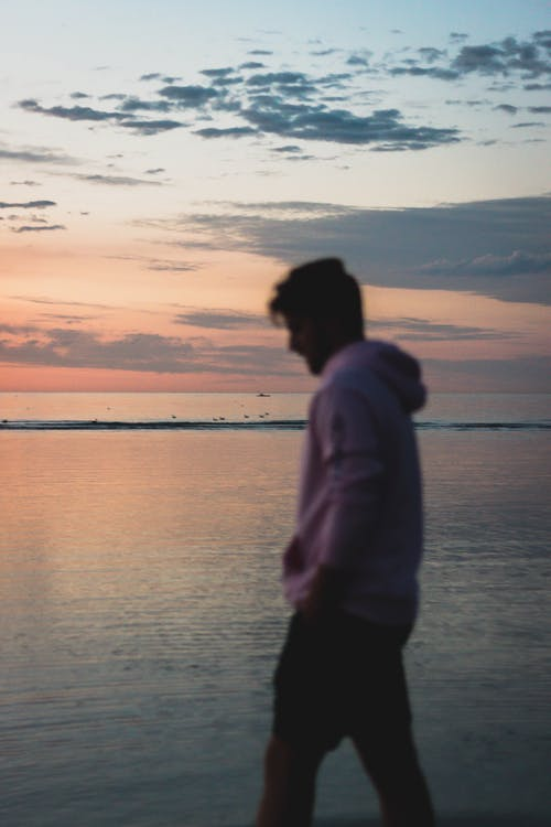 Side view of unrecognizable male traveler in pink sweater standing near calm water against cloudy sky in sunset time outside
