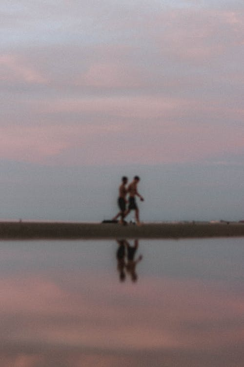 Unrecognizable people running on coast in dusk