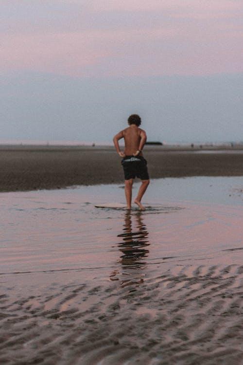 Anonymous man walking along coastline