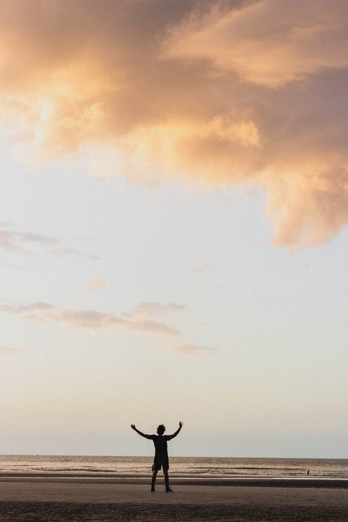 Silhouette of anonymous tourist standing on sandy coast with arms raised against sunset sky with cumulus clouds in sundown time