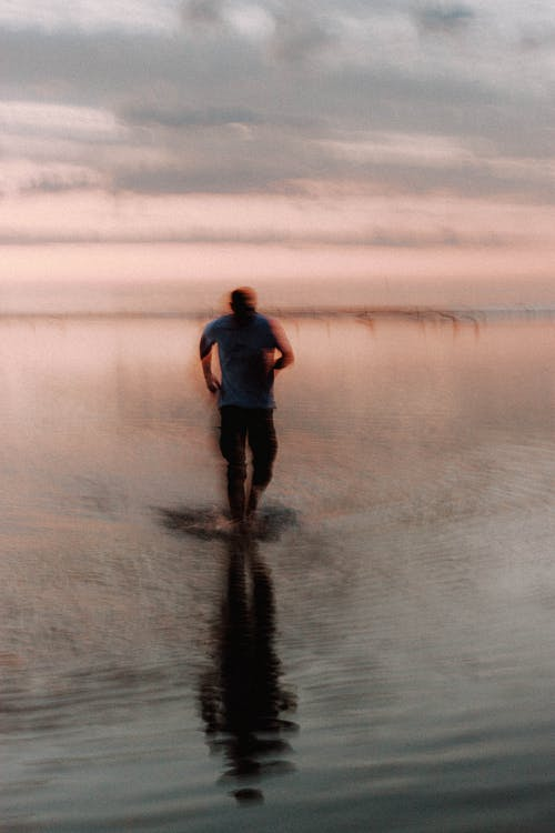 Anonymous man running in water