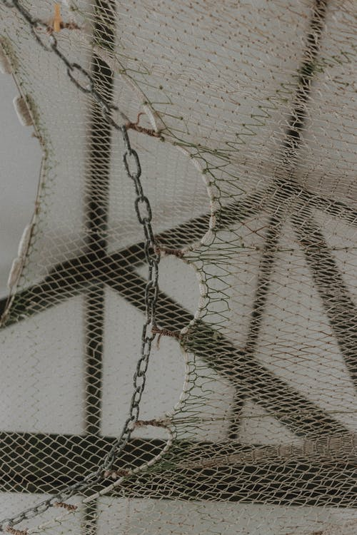 From below of net with metal chain links hanging against ceiling with wooden timber in light room in daylight on pier
