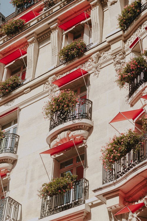 From below of facade of aged house with ornamental balconies with red canopies and flowers at sunny day