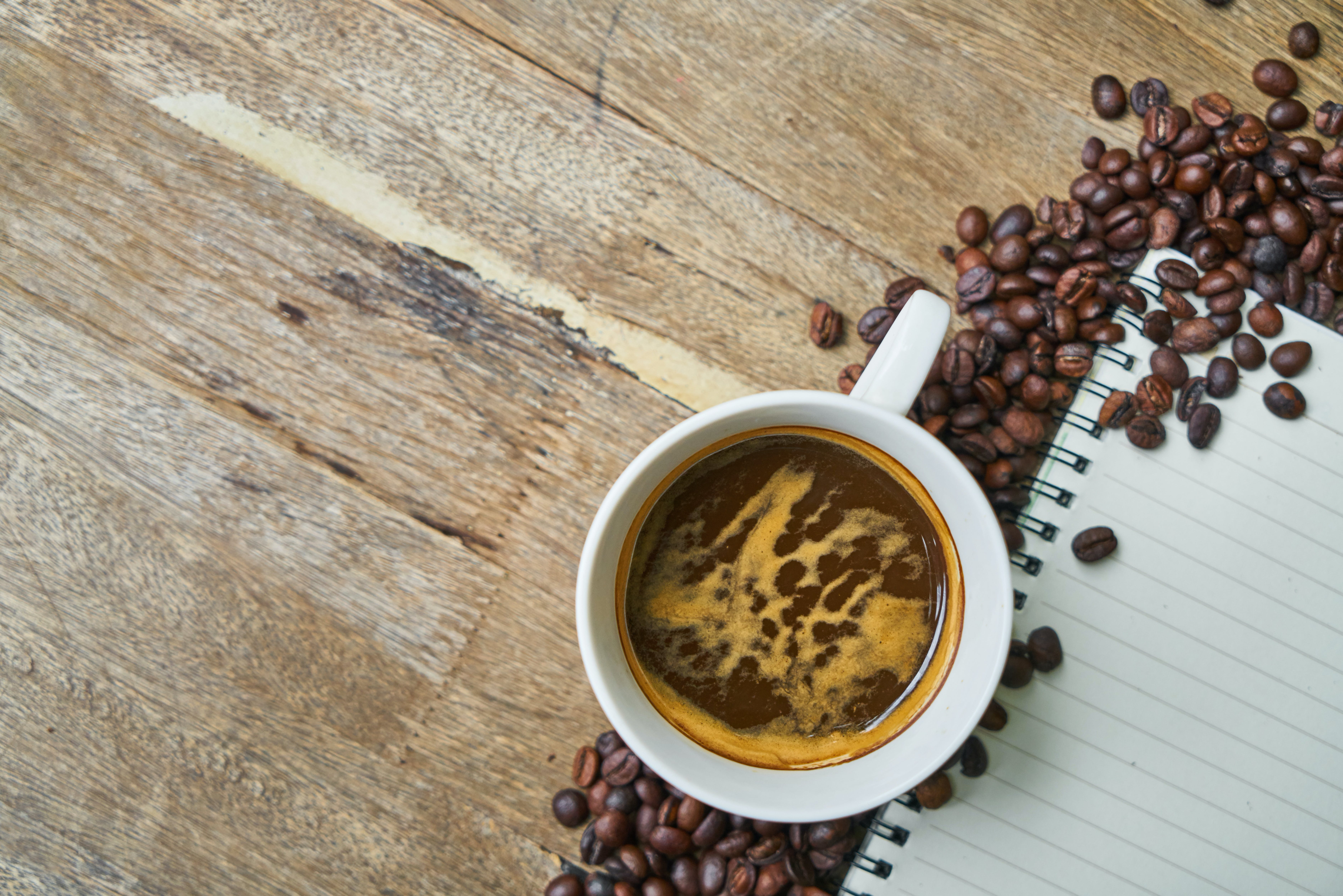 White Mug Filled With Coffee Surrounded by Coffee Beans