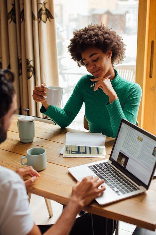 Wanita Dengan Sweater Hijau Menggunakan Macbook Pro